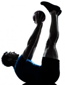 Man performs a crunch with small exercise ball