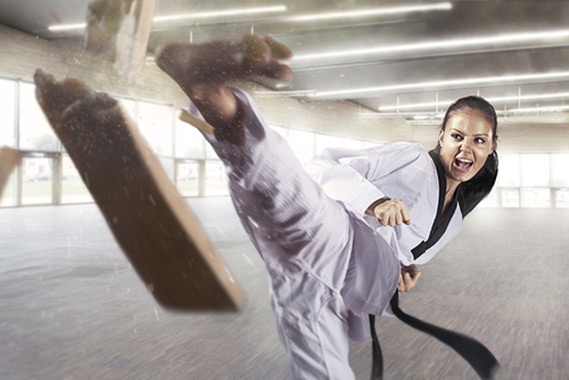 Woman breaks wood block with Judo kick
